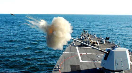 A Mk-45 Mod.4 naval gun fires a shell during a live-fire exercise. This gun can fire 20 rounds per min.