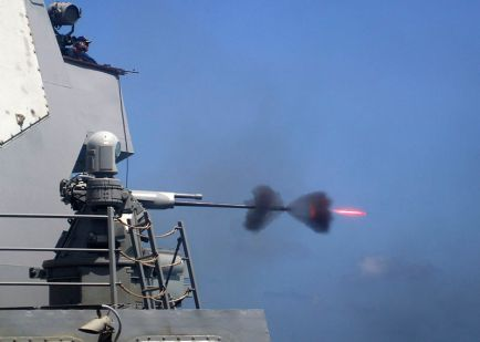 An MK-38 25mm gun system is fired during a live-fire exercise aboard the guided-missile destroyer USS Mason