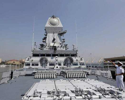 An Indian Navy personnel gestures on the deck of the newly built INS Kochi during a media tour at the naval dockyard in Mumbai